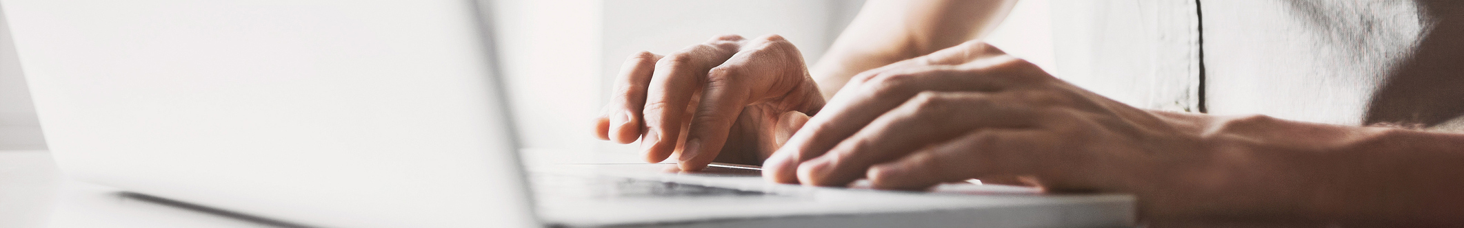 Male hands on laptop keyboard